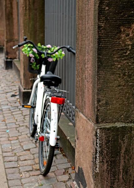 A bicycle parked along a cobblestone street in Copenhagen, Denmark