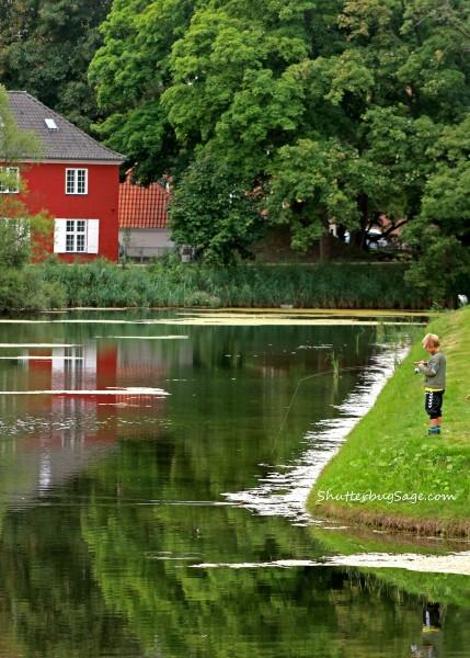 Young Danish boy fishing in the water surrounding the Kastellet in Copenhagen